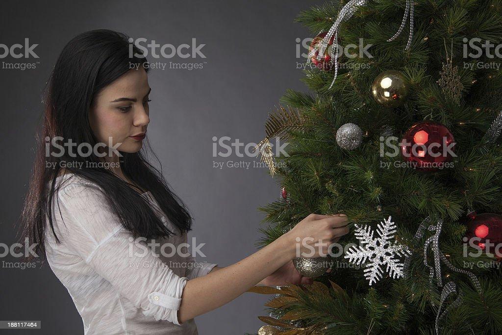 Attractive girl decorating Christmas tree stock photo