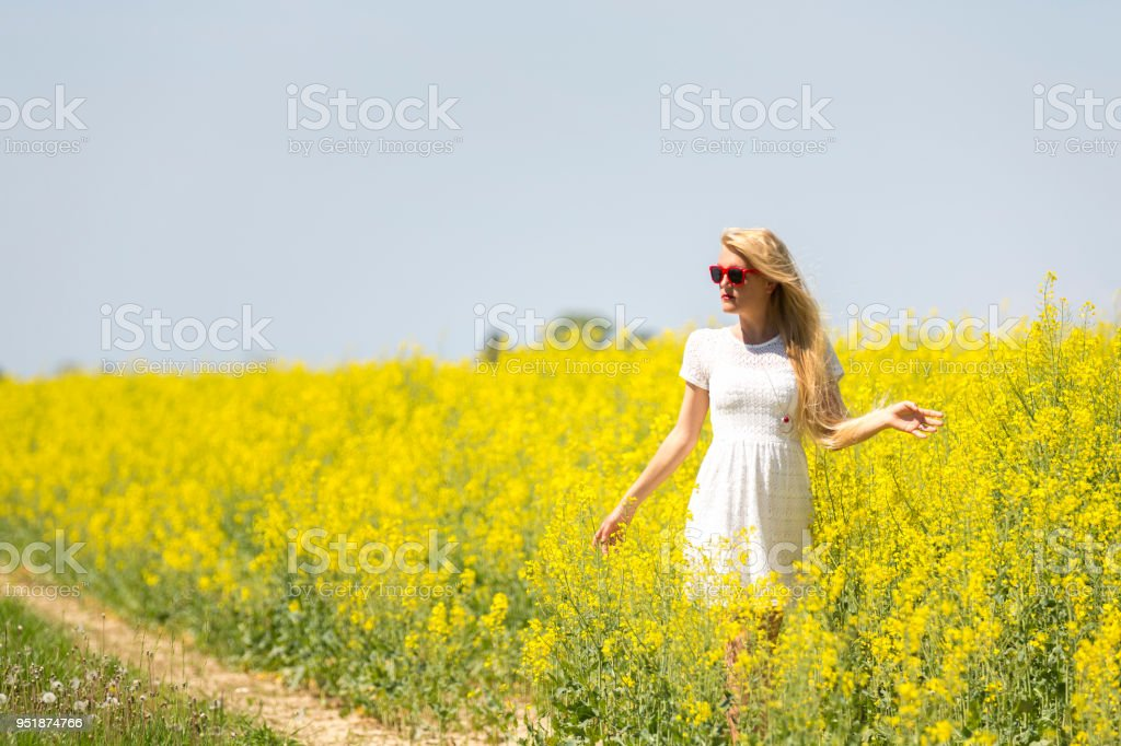 Attractive girl enjoying a walk though canola fields stock photo