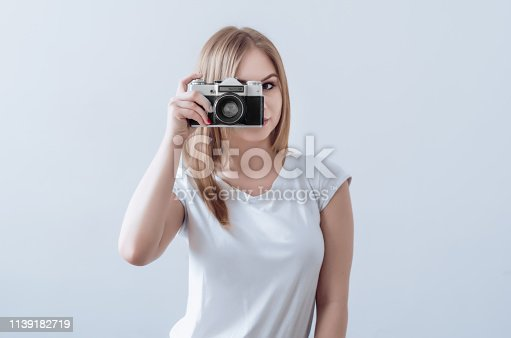 Attractive girl holding vintage camera in her hands. Take a picture.