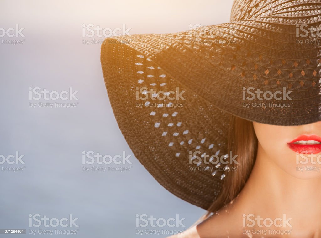 Attractive girl in a black hat worn on the head, on the beach stock photo