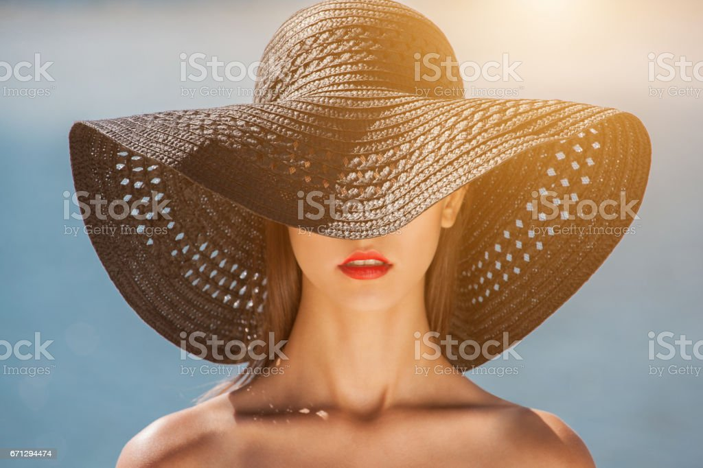 Attractive girl in a black hat worn on the head, on the beach - Foto stock royalty-free di Abbronzarsi