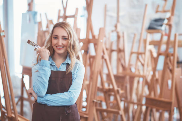 Attractive girl in an apron on the background of easels stock photo
