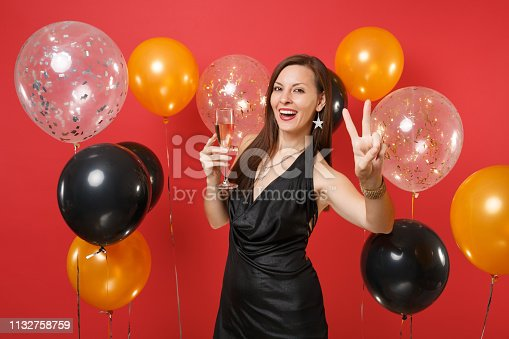 istock Attractive girl in black dress celebrating, holding glass of champagne, showing victory sign on bright red background air balloons. Women's Day, Happy New Year, birthday mockup holiday party concept. 1132758759