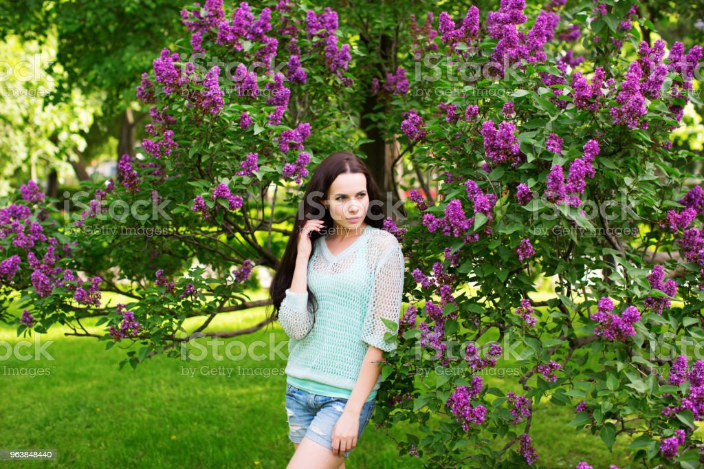 Attractive girl in the park against a flowering tree. - Royalty-free Adult Stock Photo