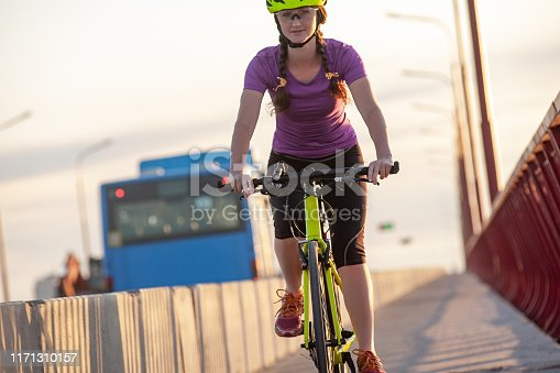 583973114istockphoto Attractive girl looking into camera while riding bicycle on road 1171310157