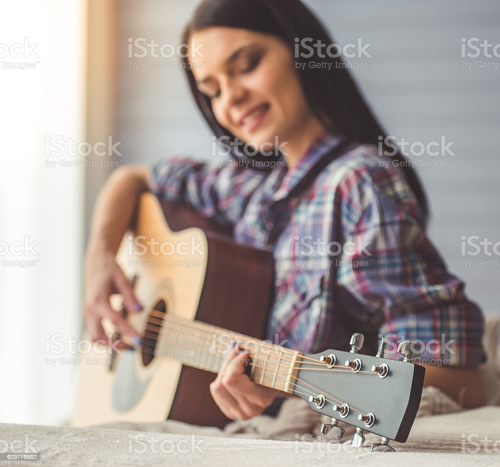 Attractive girl playing guitar stock photo