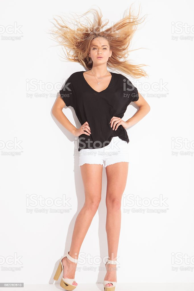 attractive girl posing while wind is messing her hair stock photo