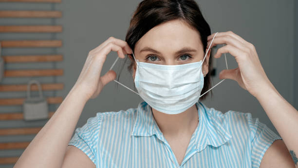 attractive girl puts on surgical mask on her face. cold, flu, virus, acute respiratory infections, quarantine, epidemic, irony, sarcasm concept. close up - mettersi lo smalto foto e immagini stock