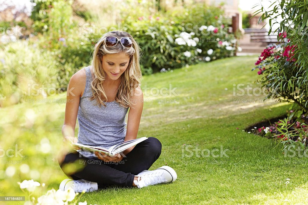 Attractive girl reading a book in the park royalty-free stock photo