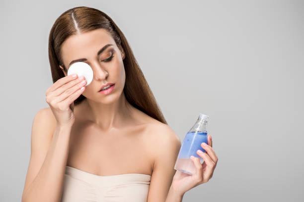 グレーに分離された綿ディスクでスキンケア製品の化粧を削除する魅力的な女の子 ストックフォト