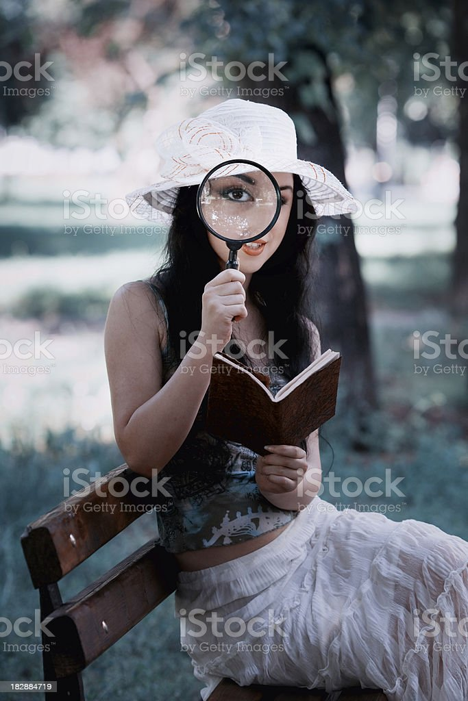 attractive girl sitting and reading book with magnifying glass royalty-free stock photo