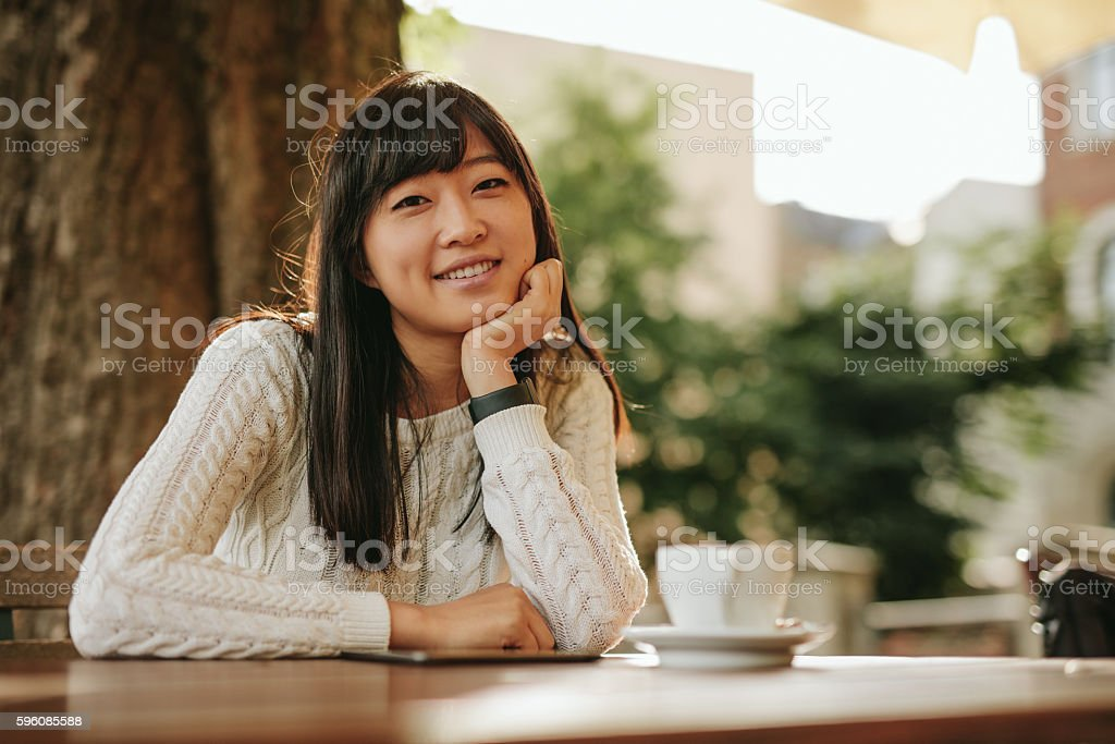 Attractive girl sitting at outdoor cafe and smiling royalty-free stock photo