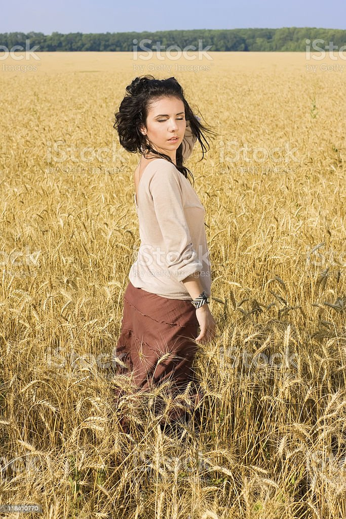Attractive girl standing in wheat field royalty-free stock photo
