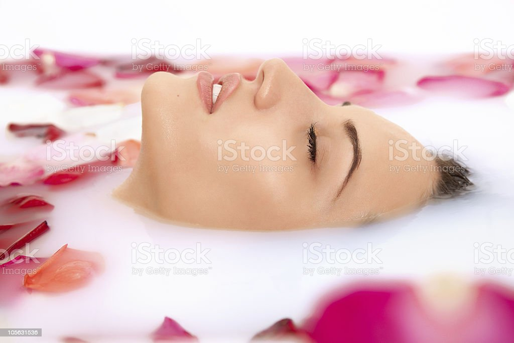 Attractive girl takes a bath with milk and rose petals stock photo
