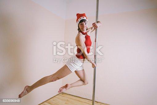 istock Attractive girl wearing Santa hat practicing pole dancing in studio 635696948