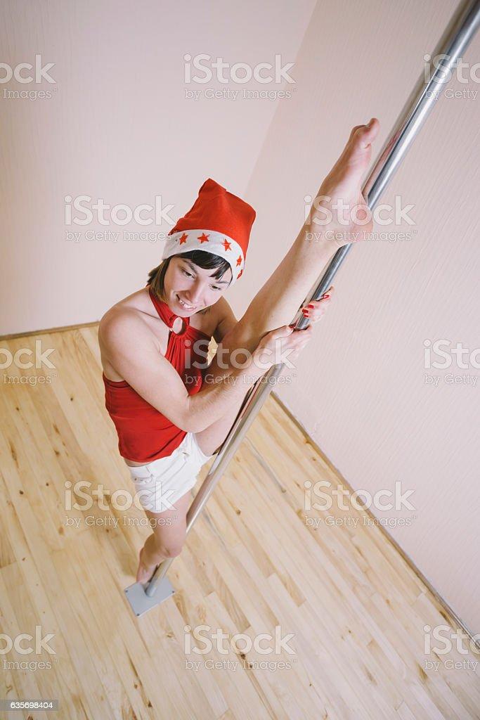 Attractive girl wearing Santa hat practicing pole dancing in studio royalty-free stock photo