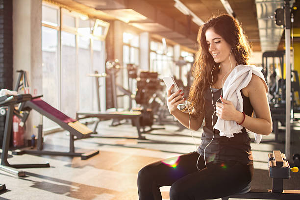Attractive girl with earphones listening to music in gym. stock photo