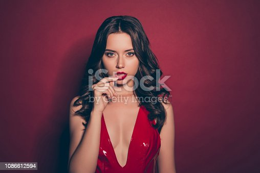 Attractive gorgeous pretty good-looking brunette lady with modern wavy hairstyle she stand in her elegant fancy lustrous shine mini wear isolated on deep red background touch low lip by fingers
