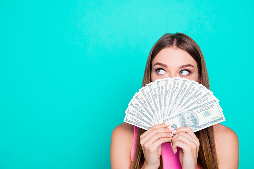 istock Attractive gorgeous young amazed girl wearing pink blouse, excited, covering face with dollar banknotes. Copy space. Isolated over bright vivid blue teal, turquoise background 1055961984