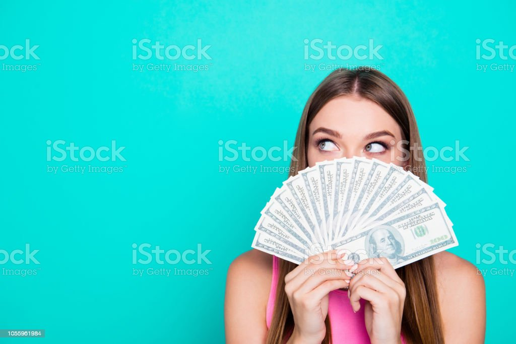 Attractive gorgeous young amazed girl wearing pink blouse, excited, covering face with dollar banknotes. Copy space. Isolated over bright vivid blue teal, turquoise background stock photo