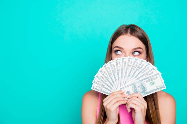 Attractive gorgeous young amazed girl wearing pink blouse, excited, covering face with dollar banknotes. Copy space. Isolated over bright vivid blue teal, turquoise background Attractive gorgeous young amazed girl wearing pink blouse, excited, covering face with dollar banknotes. Copy space. Isolated over bright vivid blue teal, turquoise background currency stock pictures, royalty-free photos & images