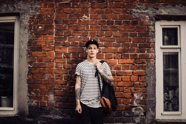 attraktiven kerl in einer kappe neben einer ziegelmauer - tatto vorlagen stock-fotos und bilder