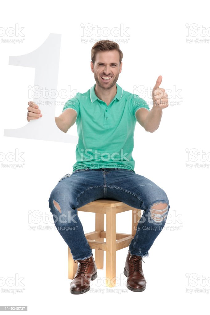 attractive guy shows ok gesture with number one sign stock photo