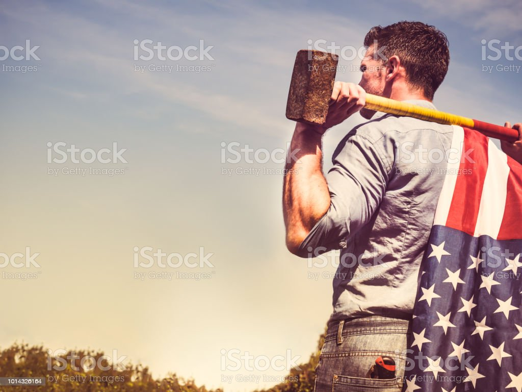 Attractive guy, sledgehammer and a US flag stock photo