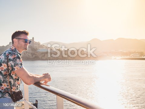 Attractive guy with a vintage camera on the deck of a cruise liner against a background of blue, sea waves, sunset and shoreline. Concept of sea cruises and rest