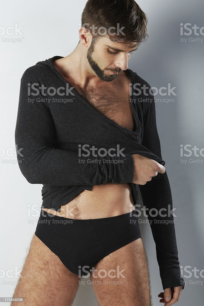 Attractive hairy man in black underwear looking down royalty-free stock photo