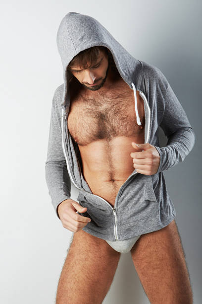 Attractive hairy man in underwear with hooded sweater looking down stock photo