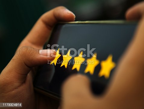 istock attractive hands showing five stars rating on a smart phone 1173324914