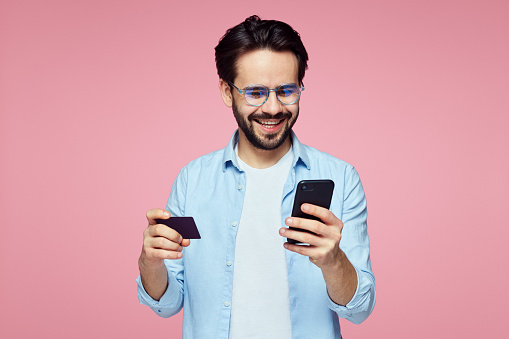 istock Attractive handsome man holding plastic credit card and mobile phone isolated over pink background. 1137960441