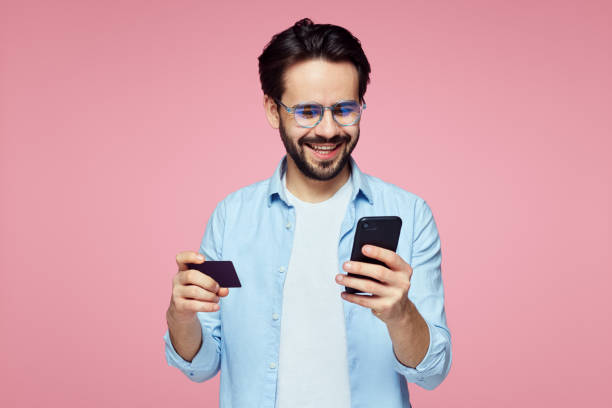 Attractive handsome man holding plastic credit card and mobile phone isolated over pink background. Closeup portrait of young bearded man holding plastic credit card and mobile phone isolated over pink background. Stylish male making shopping on smartphone phone charging stock pictures, royalty-free photos & images