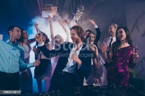Attractive, handsome man in formal wear dance with glass of beverage against crowd fancy luxury friends