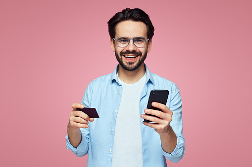 istock Attractive handsome man smiling while holding plastic credit card and mobile phone, isolated over pink background. 1142850863