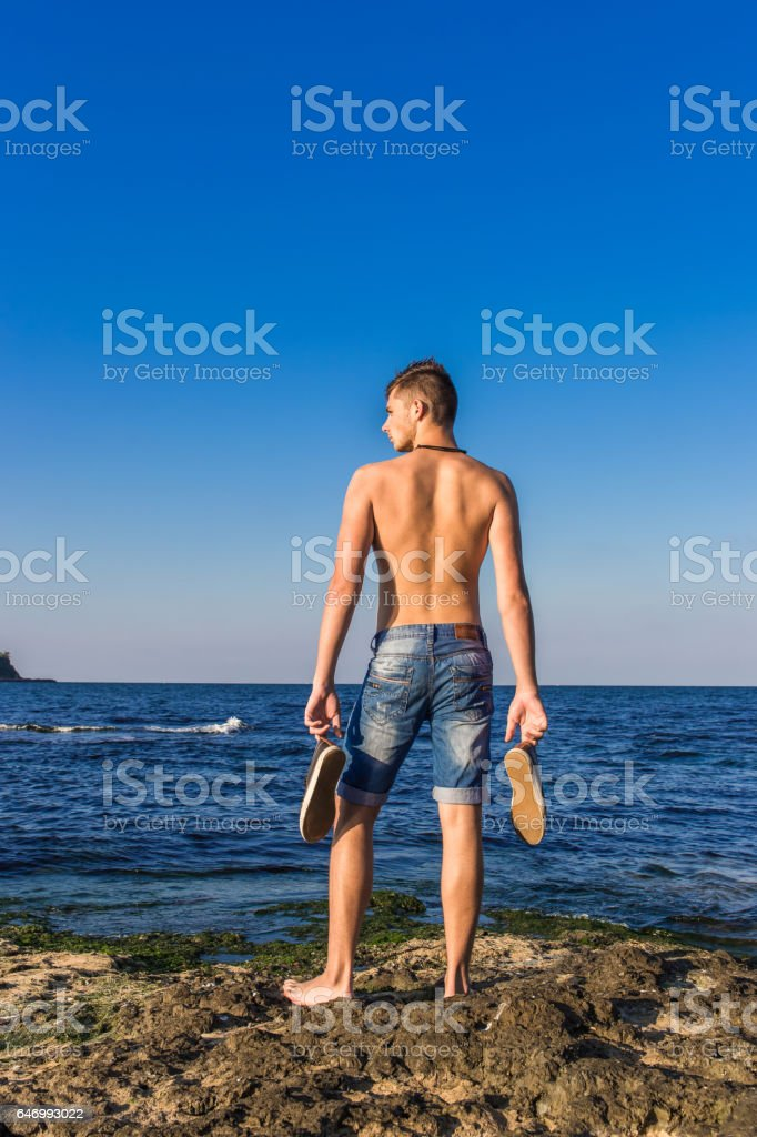 Attractive handsome sexy naked young man on rock near the sea water with shoes in hand stock photo