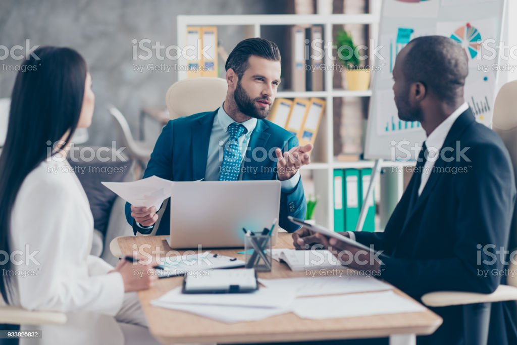 Attractive, handsome, stylish, elegant man in classic suit explaining something to his partners, three colleagues sitting in workstation, solving problems, finding solution, expertising results - Royalty-free Adult Stock Photo