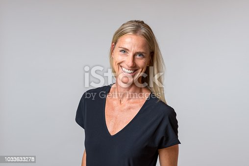 Attractive happy blond woman with a enthusiastic smile staring at the camera in a close up portrait isolated on grey