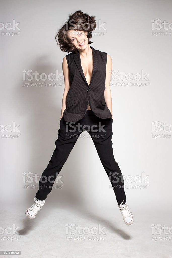 attractive happy dance model jumping in studio wearing black suit stock photo