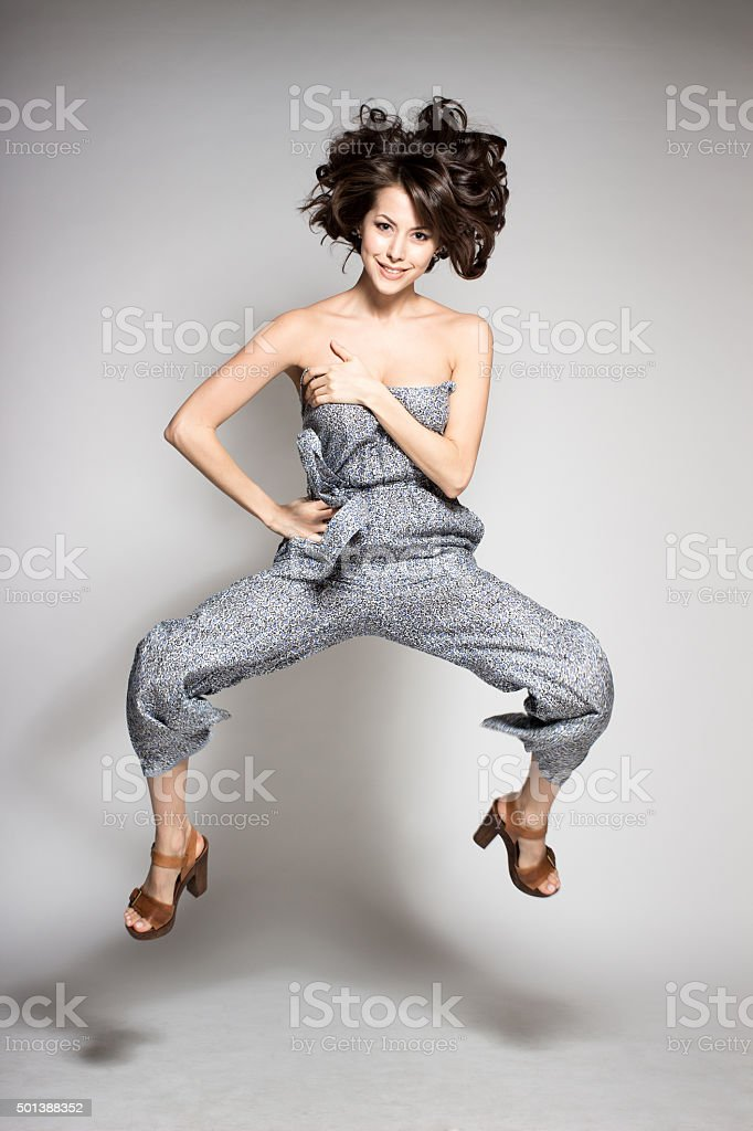 attractive happy dance model jumping in studio wearing gray overalls stock photo
