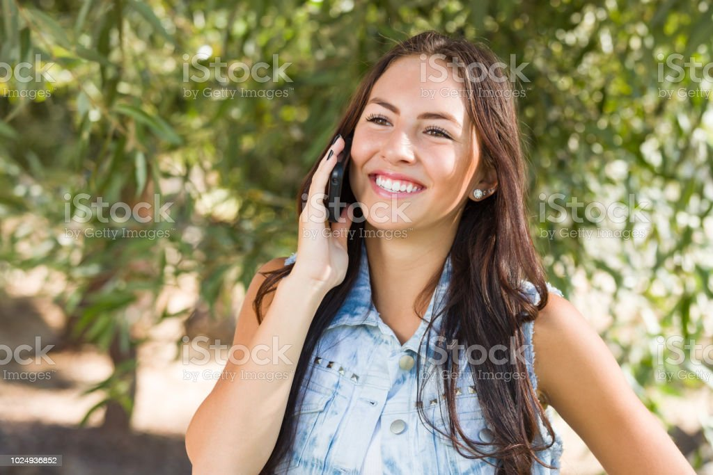 Attractive Happy Mixed Race Young Female Talking on Cell Phone Outside stock photo