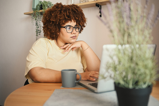 Attractive happy stylish plus size African black woman student afro hair in glasses studying online working on laptop computer at home office workspace. Diversity. Remote work, distance education