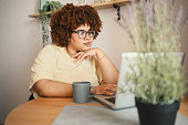 istock Attractive happy stylish plus size African black woman student afro hair in glasses studying online working on laptop computer at home office workspace. Diversity. Remote work, distance education. 1318457000