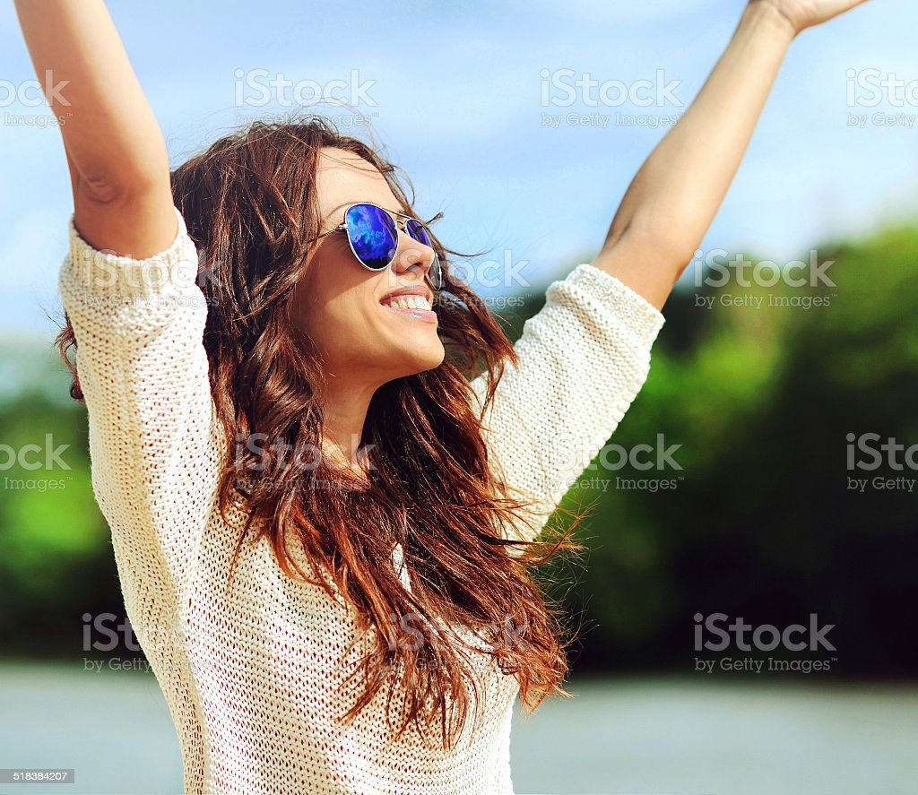 Attractive happy woman in sunglasses enjoying freedom outdoors stock photo