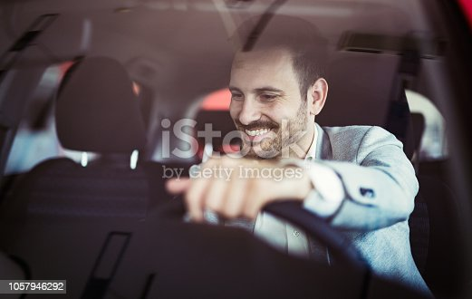 849721378istockphoto Attractive happy young man driving car and smiling 1057946292