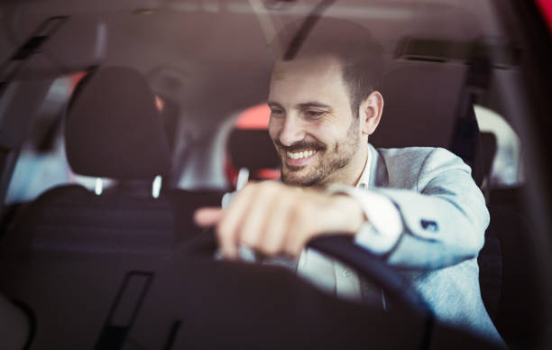 Attractive happy young man driving car and smiling stock photo