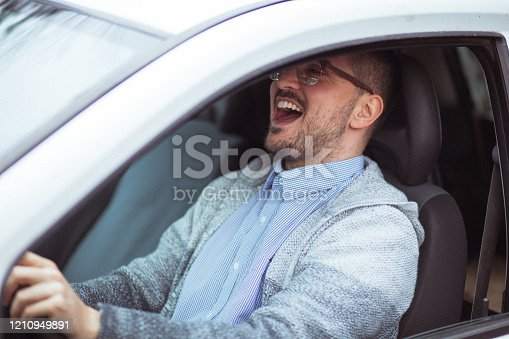 849721378 istock photo Attractive happy young man driving car and smiling 1210949891