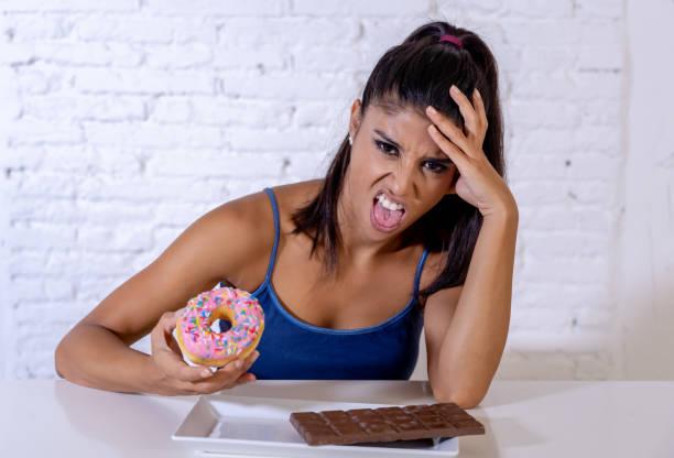ajuste saudável atraente mulher rejeitar donuts e chocolate em não mais lixo alimentos pouco saudáveis, dieta, saudável, hábitos alimentares - junk food - fotografias e filmes do acervo
