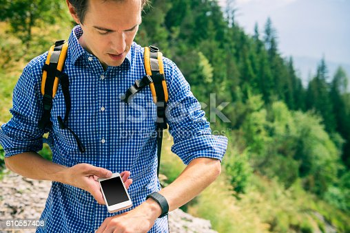 Attractive hiker in the swiss/european mountains wearing a backpack as well as an activity tracker
